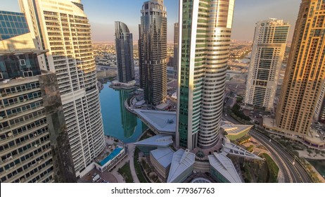 Top view of buildings Jumeirah Lakes Towers at sunset with traffic on the road timelapse. The JLT is a large development which consists of 79 towers being constructed along the edges of 3 artificial