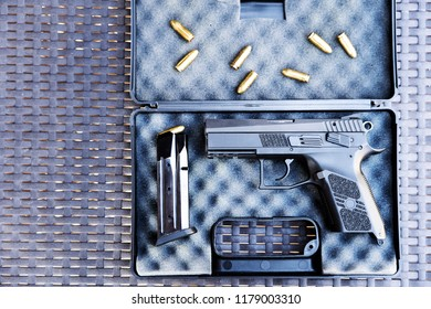 Top view of bullets and handgun. Small black pistol next to a 9 mm bullets and a magazine.
