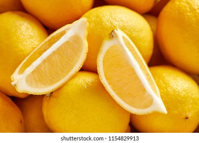 Top view of bunch of fresh lemons in the organic food market. One lemon cutted
