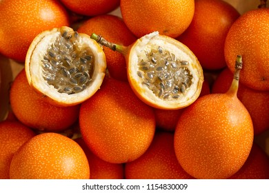 Top view of bunch of fresh passion fruit in the organic food market. One fruit cutted