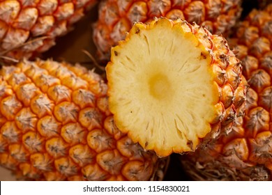 Top view of bunch of fresh pineapples in the organic food market. One pineapple is cutted
