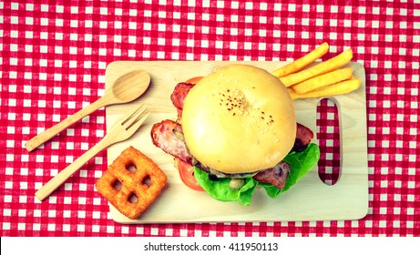Top view burger with chips on wooden board, high saturation, retro style