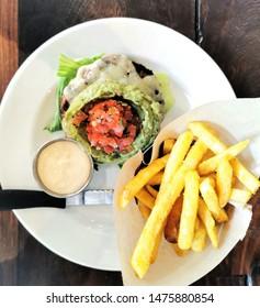 top view burger patty, avo, salsa, sauce and fries
