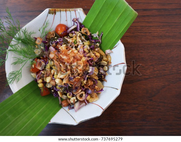 Top view of Burmese Tea Leaf Salad or Lahpet in a white plate with banana leaf on a dark wooden table