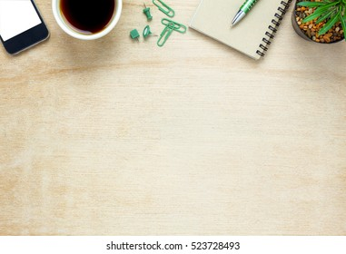 Top view business office desk.notebook,pencil,black coffee,tree,mobile phone,paperclips on wooden table background.