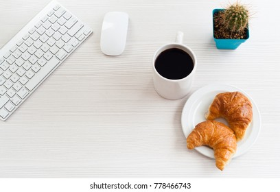 Top view business office. Keyword, coffee and croissant on white table.