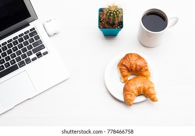 Top view business office. Laptop, coffee and croissant on white table.