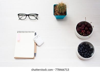 Top view business office. Notebook, coffee and fruits on white table.