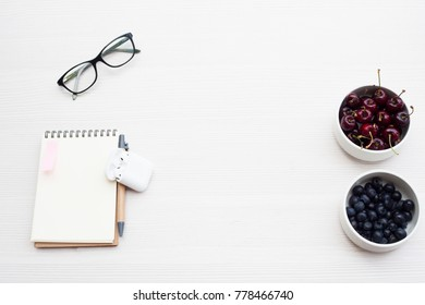 Top view business office. Notebook and fruits on white table.