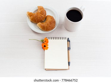 Top view business office. Notebook, coffee and croissant on white table.