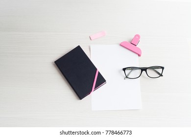 Top view business office. Notebook and glasses on white table.