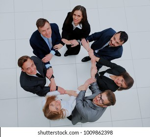 Top view of business people with their hands together in a circle.