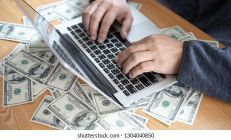 top view business people working with laptop hand typing on keyboard computer for business , us dollar bill  on office desk