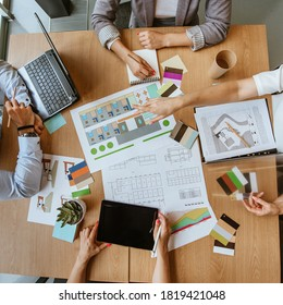 Top view of business team discussing a new hotel designer project. Documents, site plans, designer illustration, color palettes on the table.