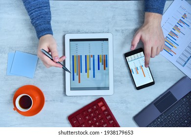 Top view of businessman doing business and charts being demonstrated on screen of a mobile phone. Success and startup concept.