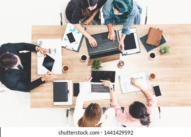 Top view of businessman executive in group meeting with other businessmen and businesswomen in modern office with laptop computer, coffee and document on table. People corporate business team concept.