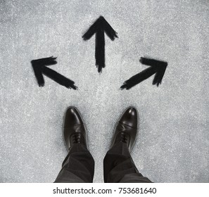 Top view of businessman feet on concrete floor with drawn arrows. Uncertainty concept