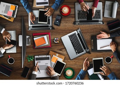 Top view of businessman Group of Multiethnic Busy People meeting with other in modern office with laptop computer, smartphone, tablet, coffee and document on table.