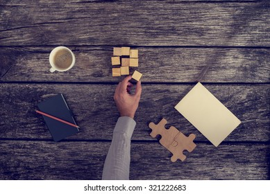 Top View of Businessman Hand Arranging Small Wooden Blocks on Rustic Table with Notes and a Cup of Coffee, Toned Retro Effect.
