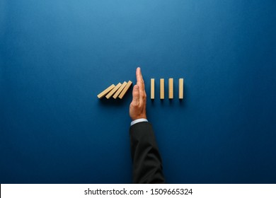 Top-Sicht auf die Hand der Geschäftsleute, die fallende Dominosteine in einem konzeptionellen Bild des Geschäftskrisenmanagements stoppen.