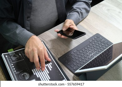 top view of businessman hand using smart phone,mobile payments online shopping,omni channel,digital tablet docking keyboard computer,documents,in modern office on wooden desk