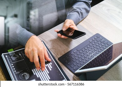 top view of businessman hand using smart phone,mobile payments online shopping,omni channel,digital tablet docking keyboard computer,document,in modern office on wooden desk,filter
