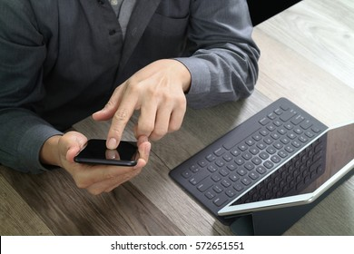 top view of businessman hand using smart phone,mobile payments online shopping,omni channel,digital tablet docking keyboard computer in modern office on wooden desk