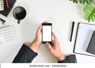 Top view businessman hands using mockup smart phone on office desk.