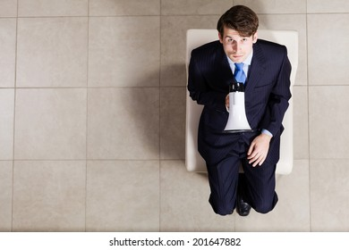 Top view of businessman sitting on chair with megaphone