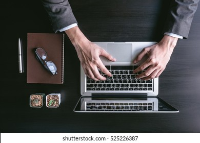 Top view of Businessman using Laptop on the black desk.