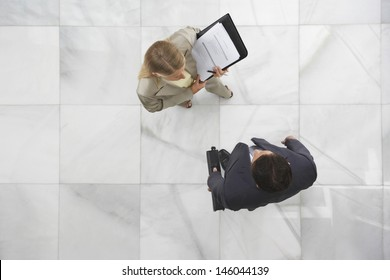 Top view of a businessman and woman conversing in office lobby
