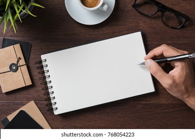 Top view of businessman writing on blank notebook. High angle view of man hand writing on empty notepad with spectacles, coffee cup and folder on wooden table. Closeup of male  hand making notes.