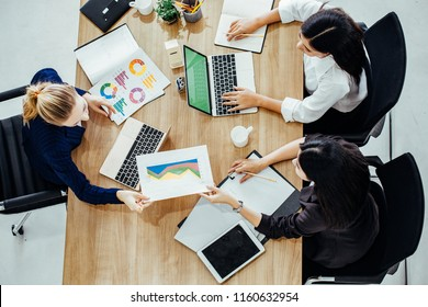 Top view of businessmen and businesswoman standing and stacking hands over table in a meeting with copy space at mobile office. Teamwork, diversity, collaboration concept.