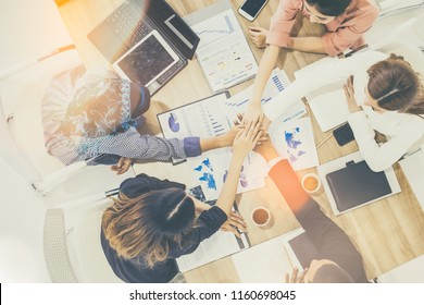 Top view of businessmen and businesswoman thumbs up over table in a meeting with copy space at mobile office.Young mixed race group of people puts palm together on the centre. Teamwork of happy guys.