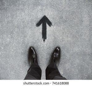 Top view of businessmen feet on concrete floor with drawn arrow. Motivation concept