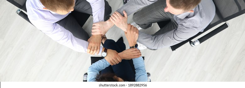 Top view of businesspeople putting hands together in office. Good deal. Support and team work. Employees sitting on chairs in stylish suits. Business and career success concept