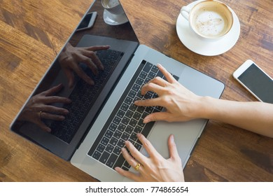Top view  businesswoman close up hand using laptop on wooden table. young girl working on notebook.female sitting at table with coffee cup and cell phone.Smart modern lifestyle technology concept.