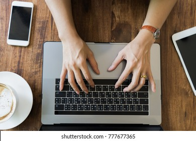Top view businesswoman hand using laptop on wooden table. young girl working on notebook.