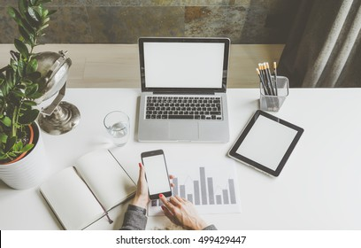 Top view of businesswoman sitting at white desk and uses smartphone.On table are laptop and digital tablet with blank screen,graph,glass of water,pencil holders,open notebook.Girl using gadget.Mock up