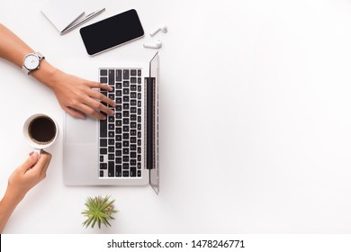 Top view of businesswoman typing on laptop on workplace and drinking coffee, copy space