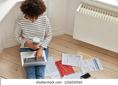 Top view of busy experienced distant worker keyboards on laptop computer, calculates costs, makes reserach work on economical topic, thinks on capital efficiency, wears srtiped sweater, drinks coffee