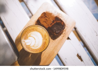 Top view of butter bun bun with cocoa powder and hot coffee on Chopping Wood.