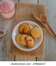 Top view of butter cookies on white cloth napkin and a glass of yogurt  with rustic wood underneath