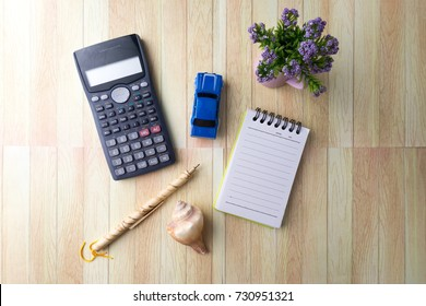 top view of calculator, toy car, flower decoration, notepad, seashell and pen