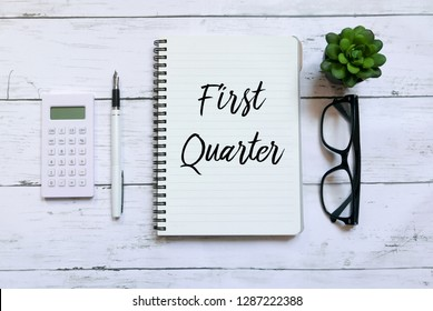 Top view of calculator,glasses,pen,plant and notebook written with First Quarter on wooden background.Business and finance concept.