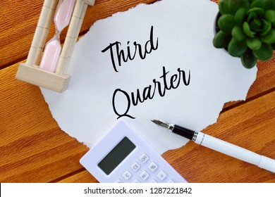 Top view of calculator,pen,sand clock,plant and paper written with Third Quarter on wooden background. Business and finance concept.