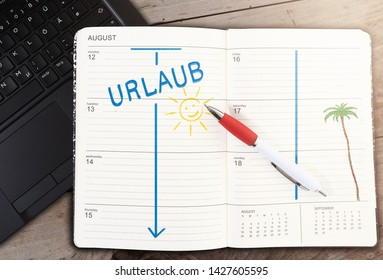 top view of calendar on table with word URLAUB, German for vacation, and sun icon against wooden table