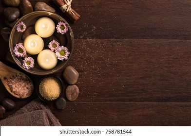 Top view of candles with salt and pebbles on wooden background with copy space. Burning candle in water with flowers, rock salt and towels at luxury spa. High angle view of aromatherapy set at salon.