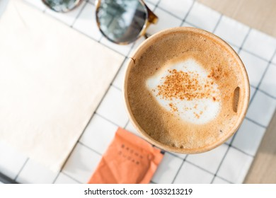 top view cappuccino in take away coffee cup on table cloth with sunglasses on wood table with sunlight hard shadow at window in evening.food and drink lifestyle leisure concept
