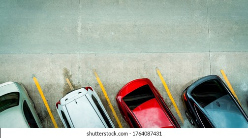 Top view of car parked at concrete car parking lot with yellow line of traffic sign on the street. Above view of car in a row at parking space. No available parking slot. Outside car parking area.